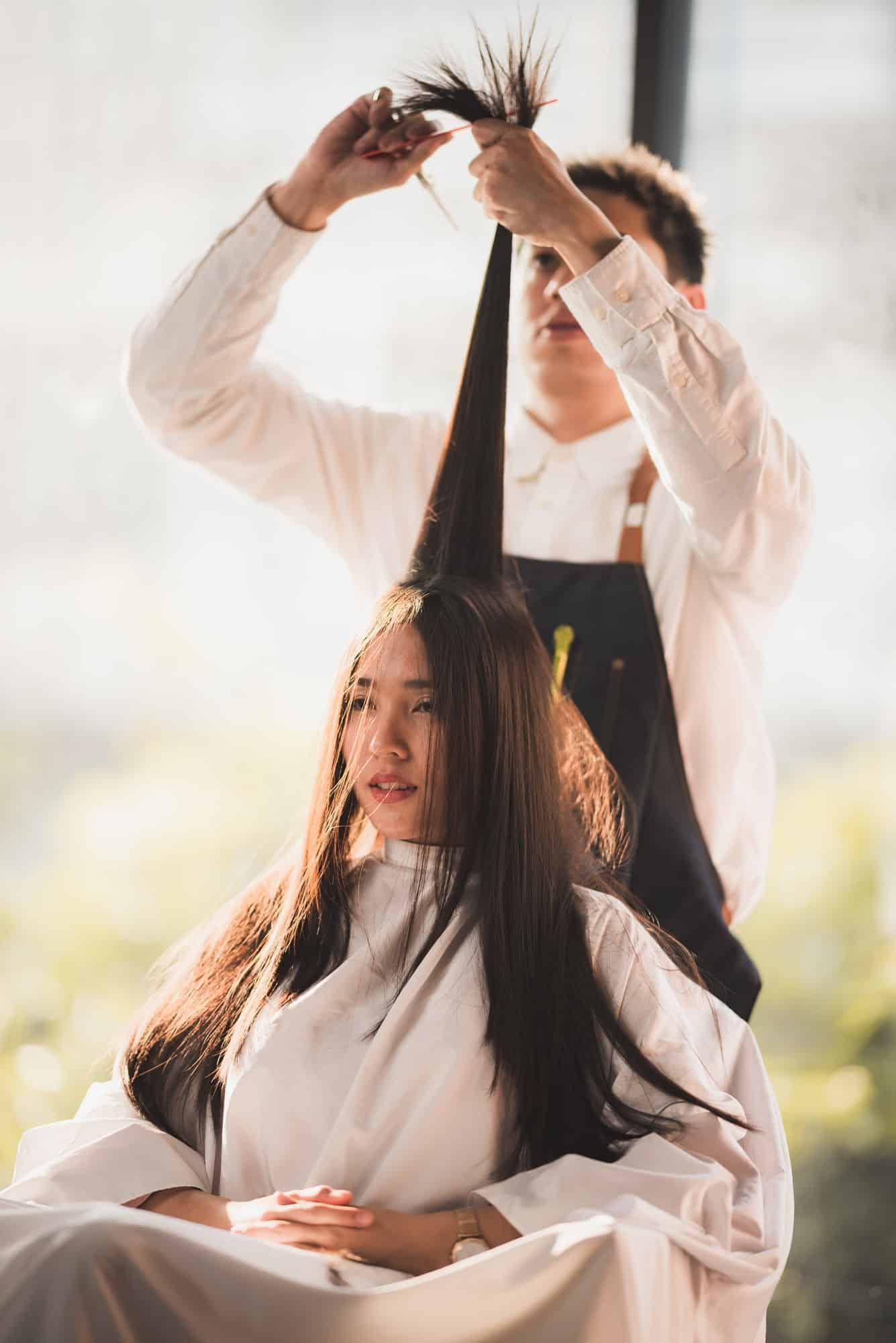 Hairdresser is cutting long hair in hair salon with scissor